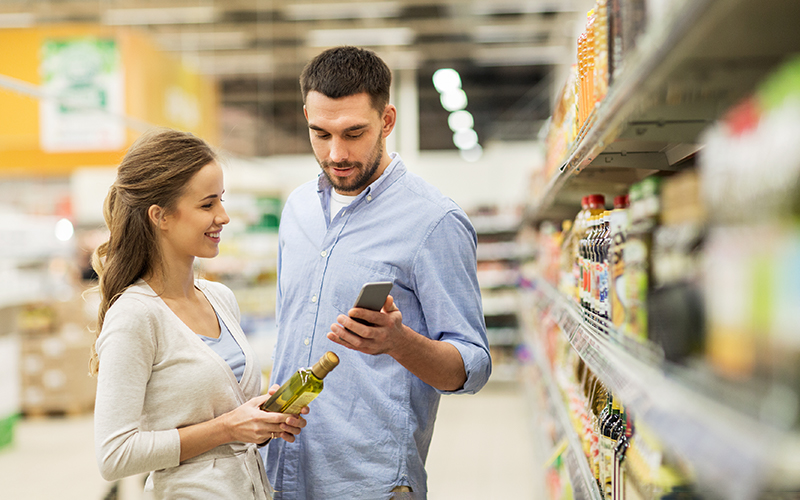 Jong koppel met smartphone in de supermarkt